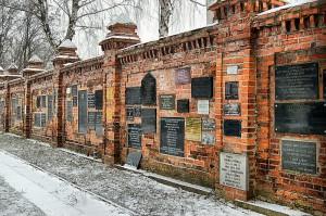 Mur cmentarny z pamiątkowymi tablicami.